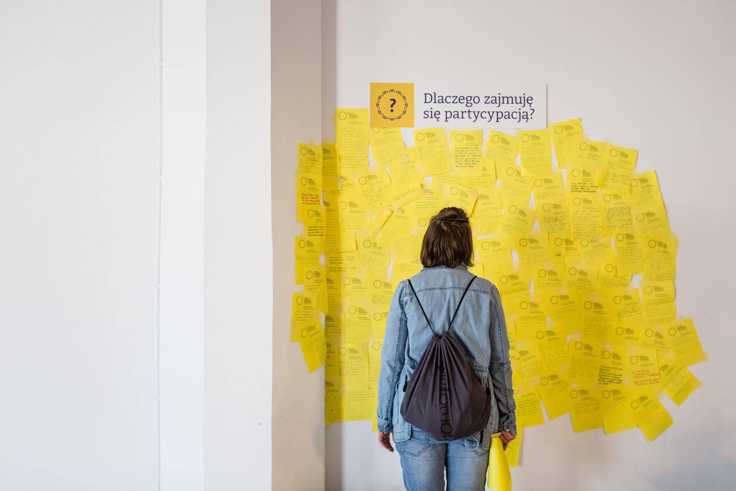 """Kobieta stoi przed ścianą, na której wisi tabliczka z pytaniem """"Dlaczego zajmuję się partycypacją? i samoprzylepne karteczki z różnymi odpowiedziami na nie"""